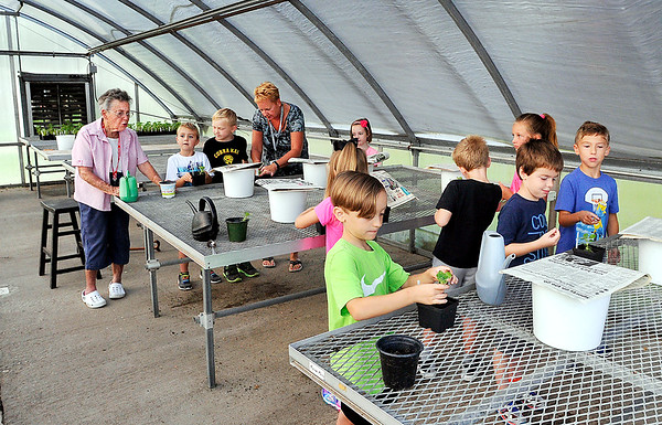 John P. Cleary | The Herald Bulletin<br /> Retired teacher Marilyn Crosley conducts an outdoor gardening program for Pendleton Elementary students. Here Crosley, far left, gives instructions to Missy Petro's first grade students on planting their Vicks plant.