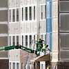 John P. Cleary   The Herald Bulletin<br /> Workers use a lift to apply a coating of paint onto the exterior of the Fieldhouse Apartments being built on West 14th Street next to the Wigwam Monday afternoon.