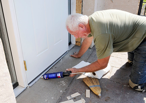 Don Knight   The Herald Bulletin<br /> Al Gullion calks around a new door he installed at Beverly Terrace Apartments on Wednesday. Work on the first two floors should be done by the end of the year.