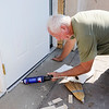 Don Knight | The Herald Bulletin<br /> Al Gullion calks around a new door he installed at Beverly Terrace Apartments on Wednesday. Work on the first two floors should be done by the end of the year.