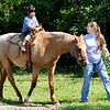 Don Knight | The Herald Bulletin<br /> Jennifer Johnson leads Jazz as Kathy Soriano, 7, goes for a ride during the Friends of the Poor Walk at Highland Middle School on Saturday.