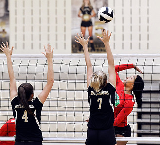 John P. Cleary | The Herald Bulletin Anderson's Tiara Ingram, right, jumps to attempt a kill as Lapel's Zoe Freer and Lexi Anderson defend the net.