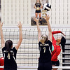 John P. Cleary | The Herald Bulletin<br /> Anderson's Tiara Ingram, right, jumps to attempt a kill as Lapel's Zoe Freer and Lexi Anderson defend the net.