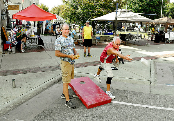 John P. Cleary | The Herald Bulletin<br /> Steve Kempher, right, takes his shot as Paul Keesling waits his turn as they compete in the cornhole tournament Saturday at the Animal Protection League's Pawapalooza at Dickmann Town Center. This is APL's second Pawapalooza fund raising event.