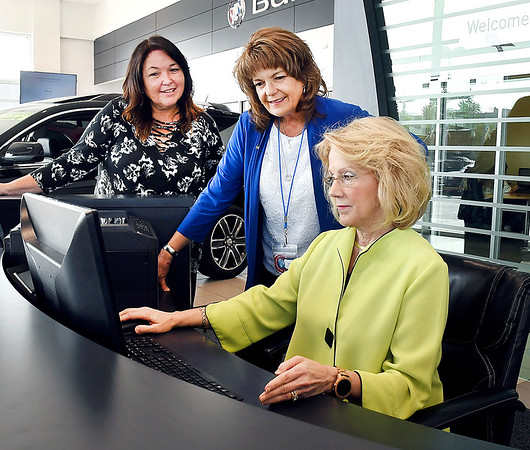 John P. Cleary | The Herald Bulletin<br /> Mary Jamerson, right, owner of Myers Autoworld, goes over items with dealership guest advisors, Wendy Santos and Lindy Burgan-Forrester.