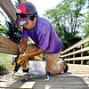 John P. Cleary | The Herald Bulletin<br /> Meliton Santigo secures a loose board along the boardwalk near Grand Avenue Tuesday. Santigo works for Bautista Landscaping who is refurbishing the boardwalk from north of Eisenhower Bridge to Shadyside Park. They have pressure washed the wood and are now securing loose pieces, or replacing bad ones, then will put a sealant on the wood.