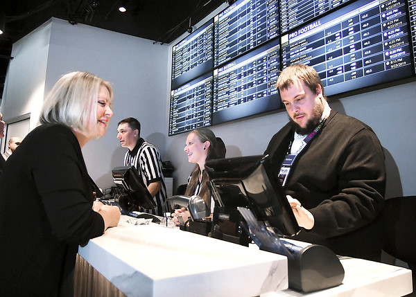 John P. Cleary | The Herald Bulletin<br /> Rep. Terri Austin watches as sport book writer Matthew Rinehart enters her wager on the Colts into the system Thursday at The Book, the new sports betting area at Harrah's Hoosier Park Racing & Casino.
