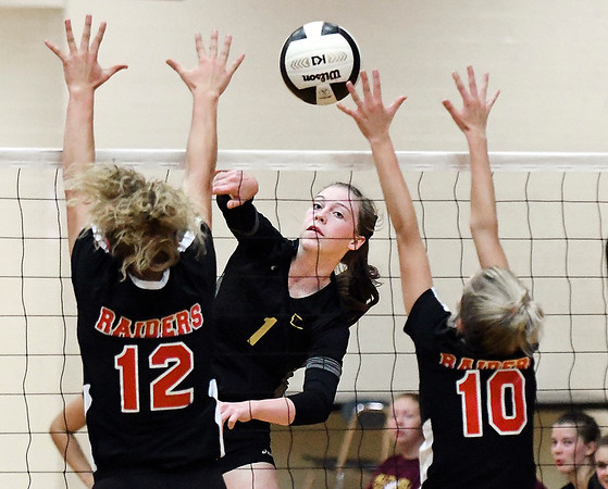 John P. Cleary | The Herald Bulletin<br /> Alexandria's Kaitlyn Bair gets one of her kills between Raider defenders Camryn Wise and Bryleigh Felton.