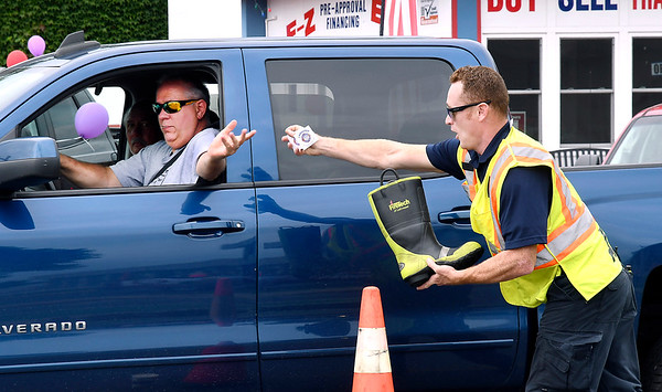 John P. Cleary | The Herald Bulletin<br /> Anderson Fire Department fireman Landen Henson stretches to give this driver their I Donated sticker as he starts to pull away as the light turns green at Fifth and Jackson Streets Saturday afternoon. Anderson Fire Department personnel were out collecting for the Muscular Dystrophy Association in the Fill The Boot campaign over Labor Day weekend.