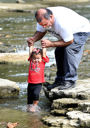John P. Cleary | The Herald Bulletin<br /> With the help of grandpa, Louis Flores, Alaina Flores, 18 months, gets to dangle her feet in the waters of Fall Creek Saturday in Pendleton. Flores was watching his granddaughter and decided to go play in the park with her.