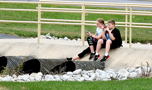 John P. Cleary | The Herald Bulletin<br /> Emily Gooding and her brother Aden, both 12, relax as they sit along the edge of this foot bridge at Lapel High School checking their phones Wednesday after school. They were at the school to watch their older brother play sports.