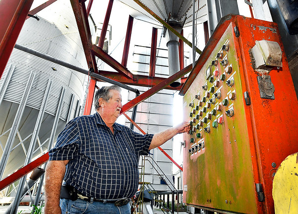 John P. Cleary | The Herald Bulletin<br /> Milke Shuter, of Shuter Sunset Farms, checks the control panel for the grain silos.