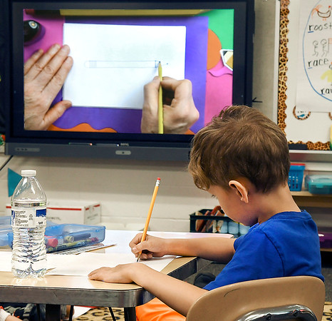 John P. Cleary | The Herald Bulletin<br /> Students from Samantha Smith's Summitville Elementary School kindergarten class watch, and follow a video showing the proper way to hold a pencil or crayon and teaching cursive writing.