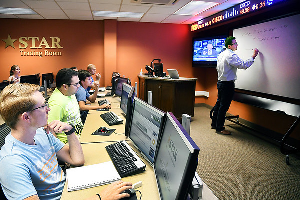 John P. Cleary | The Herald Bulletin<br /> Anderson University professor, Dr. Brock Vaughters, goes over several points with his investment class students in the Star Trading Room this past week.