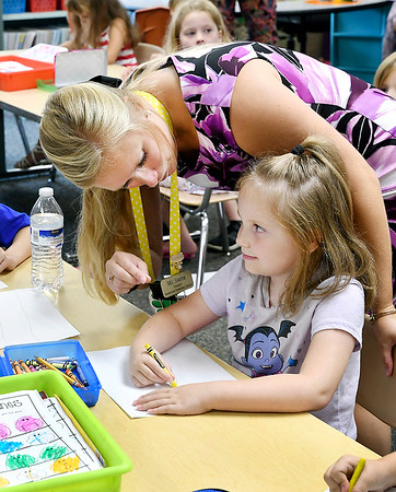 John P. Cleary | The Herald Bulletin<br /> Summitville Elementary School kindergarten teacher Samantha Smith assists Emma King with holding her crayon as the class follows a video.