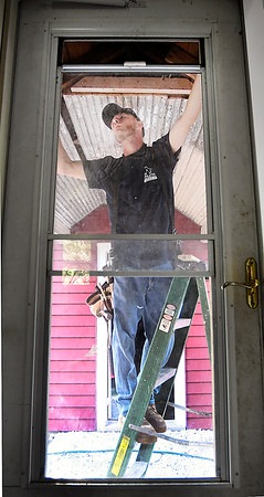 John P. Cleary | The Herald Bulletin<br /> Mike Myers, Big Head Industry team member, measures above the doorway as he replaces wood pieces for the breezeway on the house they are remodeling on West 11th Street.