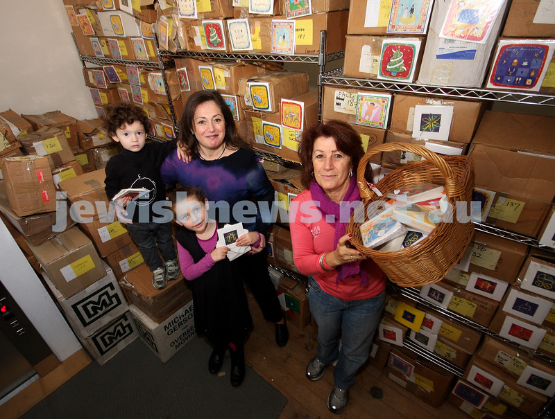Rosalie Silverstein (right) from the Posh Op Shop with some of the 200,000 greeting cards donated  by Elana Rubenstein, who is pictured here with her children Osha and Zofi Rubenstein-Slesenger. Photo: Peter Haskin