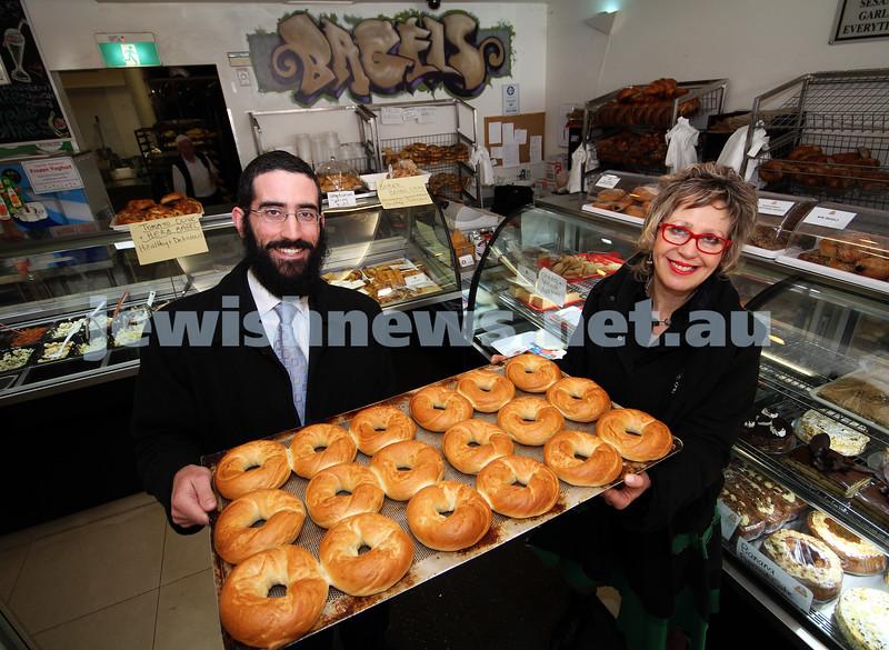7-10-10. Glick's. Rabbi Yakov Glassman hands over bagels to Deborah Wiener from the Jewish Task Force Against Violence. Photo: Peter Haskin