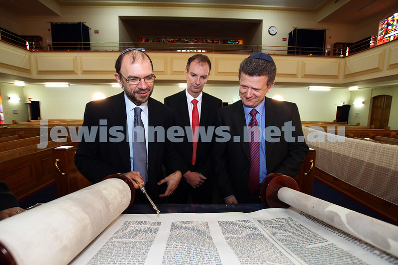 10-8-11. Victorian Minister for Multicultural Affairs and Citizenship Nicolas Kotsaris visits Caulfield Shul. Rabbi Ralph Genende (left) showing the minister one of the shul's sefer torah. David Southwick looks on. Photo: Peter Haskin
