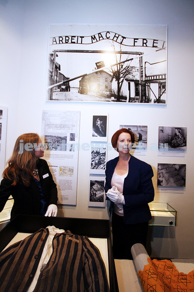 """26-7-12. Australian Prime Minister Julia Gillard tours the Jewish Holocaust Museum and Research Centre with Head Curator Jane Josem.  Looking at a roll of fabric with the """"Jude"""" star printed on it and a Concentration Camp uniform. Photo: Peter Haskin"""