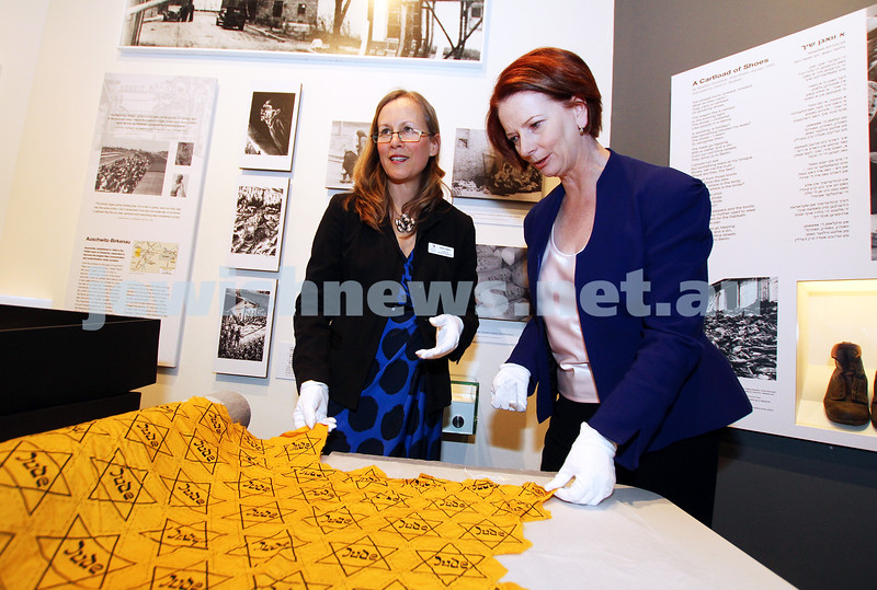 """26-7-12. Australian Prime Minister Julia Gillard tours the Jewish Holocaust Museum and Research Centre with Head Curator Jane Josem.  Looking at a roll of fabric with the """"Jude"""" star printed on it. Photo: Peter Haskin"""