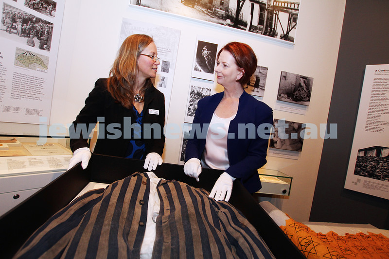 "26-7-12. Australian Prime Minister Julia Gillard tours the Jewish Holocaust Museum and Research Centre with Head Curator Jane Josem.  Looking at a roll of fabric with the ""Jude"" star printed on it and a Concentration Camp uniform. Photo: Peter Haskin"