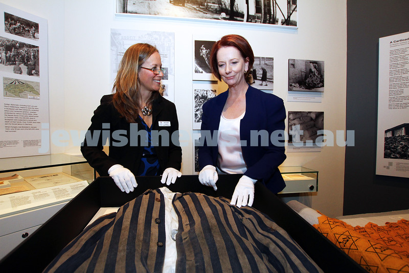 """26-7-12. Australian Prime Minister Julia Gillard tours the Jewish Holocaust Museum and Research Centre with Head Curator Jane Josem.  Looking at a roll of fabric with the """"Jude"""" star printed on it and Concentration Camp uniform. Photo: Peter Haskin"""