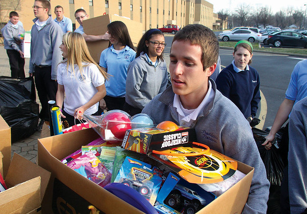 Providence High School junior Aaron Patterson loads some of the nearly 2,400 new toys collected by the school's students and donated to the Salvation Army Toys for Tots program.   Staff photo by C.E. Branham