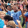 Parkwood Elementary School second-grader Kweli Coleman, center, and more than 500 classmates and staff did jumping jacks for one minute Wednesday as participants in Let's Jump.  The nationwide event is an attempt by First Lady Michelle Obama to break the Guinness Book of World Records for most people doing jumping jacks in a 24-hour period.  Staff photo by C.E. Branham