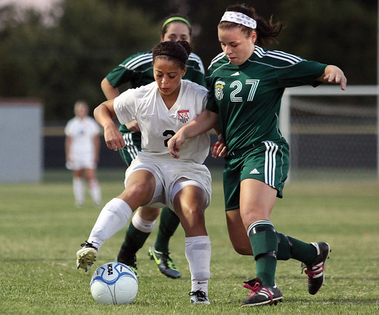 Floyd Central forward Kady O'Farrel pressures New Albany forward Kamaren Cole in the opening game of the 2A soccer sectional at Jeffersonville.  Staf photo by C.E. Branham