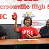 Jeffersonville High School senior Jalynn McClain waves WKU towel Wednesday after signing a letter of intent to play college basketball for Western Kentucky University.  Jalynn's mother Rhonda McClain is seated left and Mac Owens is seated right.  Staff photo by C.E. Branham