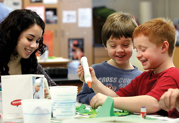 Nicholas Prince, center, and Zachary Hoffman work with New Albany High School student Cicely Calilung at the school's annual Children's Holiday Art Workshop.  Staff photo by C.E. Branham