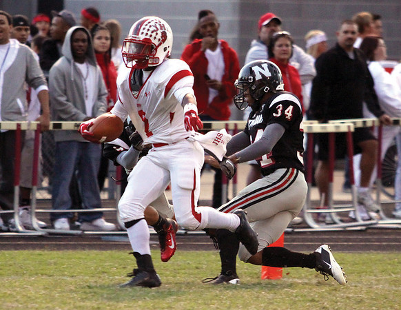 Jeffersonville running back Austin Hines carries in for a 17-yard touchdown with New Albany defenders Marquil Hastings (34) and Keaton Stout in tow.  Staff photo by C.E. Branham