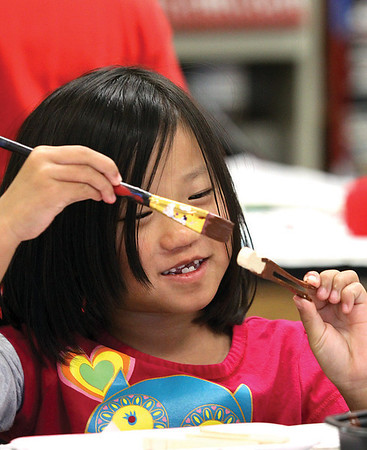 Lilli Hollis paints a clothes pin for a reindeer ornament at the New Albany High School annual Children's Holiday Art Workshop.  Staff photo by C.E. Branham
