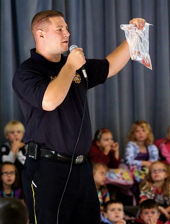 Jeffersonville fire chief David Kaskie holds up a bag of matches as he discussed fire safety with students at Thomas Jefferson Elementary Friday morning.  Staff photo by C.E. Branham