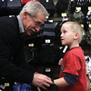 Jim Butner fits Adam Braid with a pair of gloves during the New Albany Police Department Cops for Kids.  Staff photo by C.E. Branham