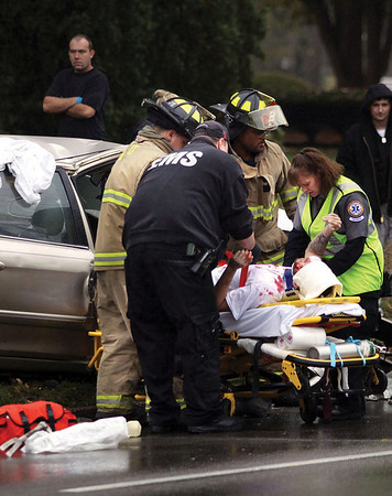 A passenger in a gold four-door Kia involved in an accident with a Jeffersonville Police cruiser is transported to the hospital Thursday afternoon after being extricated.  Staff photo by C.E. Branham