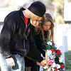 Brandon Reardon, left, Marissa Samons, center and Jasmine Fields place a wreath on the grave of WWII Navy veteran Donald G. Alldaffer.  Alldaffer's great-grandson Chris Alldaffer is a member of the New Albany High School Navy JROTC program.  Staff photo by C.E. Branham