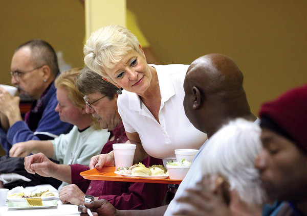 Volunteer Susan Allen serves dinner to a guest at the Community Kitchen in Jeffersonville Thanksgiving day.  Staff at the kitchen expected to serve more than 300 meals.  Staff photo by C.E. Branham