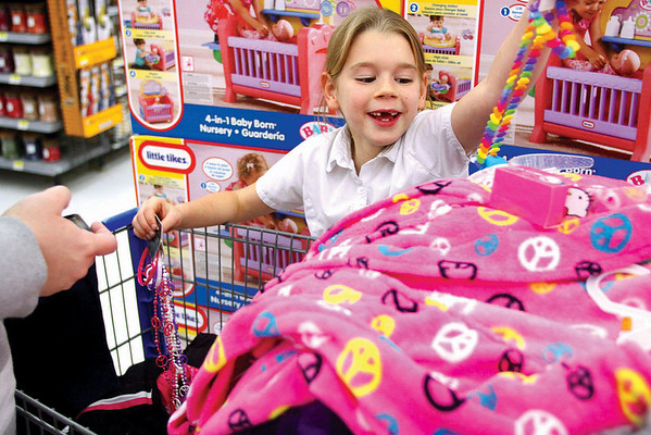 Destinie Blankenbaker moves her items to make room for a doll nursery while shopping with the New Albany Police Department Wednesday at the Wal-Mart in New Albany.  Sixty children were treated to $200 of clothes, toys and dinner as part of the department's annual Cops for Kids program.  Staff photo by C.E. Branham