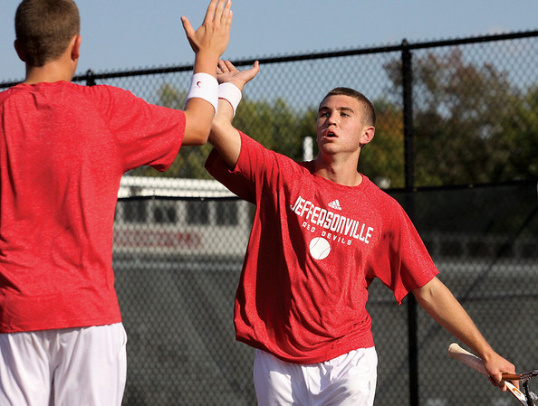 Jeffersonville no. 1 doubles player Justin Padgett and partner Austin Hunt celebrate a point in the Jeffersonville Tennis Sectional Thursday.  Staff photo by C.E. Branham