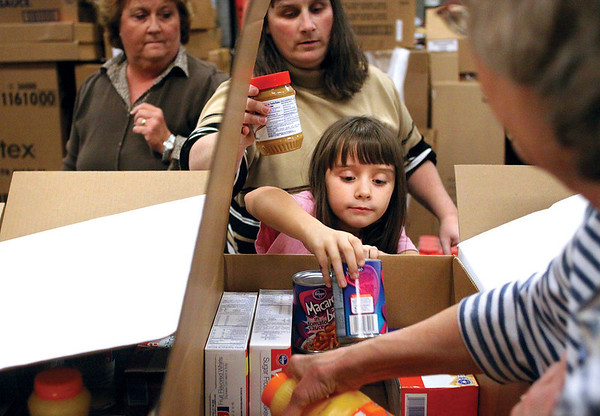 Bailey Shafer helps fill a food box for the Jeffersonville Kroger's annual Feeding Families program. Volunteers put together 260 boxes of of food for students on the free and reduced lunch programs.  Staff photo by C.E. Branham