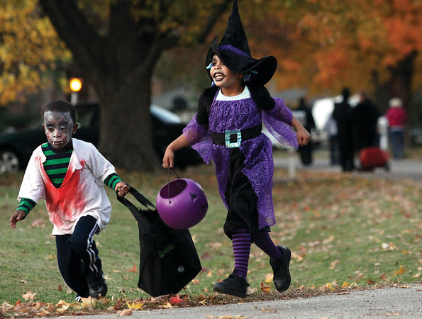 Jordan Sims, left, and Amia Bullitt run to collect another treat in Oak Park subdivision Halloween night.  Staff photo by C.E. Branham