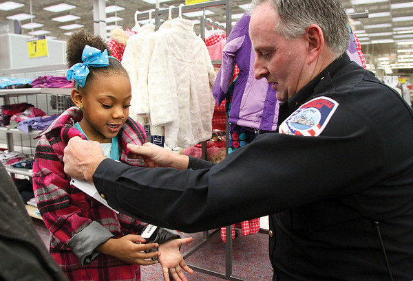 Jeffersonville police officer Mark Lovan puts a coat on E'Tiajah Williams while shopping at Meijer Monday afternoon.  The Jeffersonville Police Department took 20 kids on a $300 holiday shopping spree for clothes and toys.  The kids also were treated to dinner at the Jeffersonville Elks Club.  Staff photo by C.E. Branham