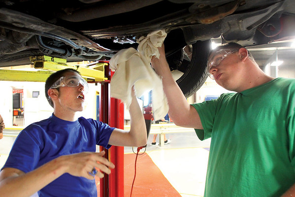 Josh Watson, left, and Jeff Palmer wipe grime off a transmission to find a leak while working in the  Greater Clark County Schools Automotive Services Technology Program.  Staff photo by C.E. Branham