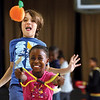 Maple Elementary School fifth-graders James Pasierbowicz and Danaeja Brown sling a soft pumpkin at a target Tuesday in their gym class.  The students have 12 halloween theme stations involving team work and coordination skills.  Staff photo by C.E. Branham