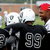 New Albany football player Scootie Middleton talks with players on the New Albany Youth Football League Raiders team last weekend.  Staff photo by C.E. Branham