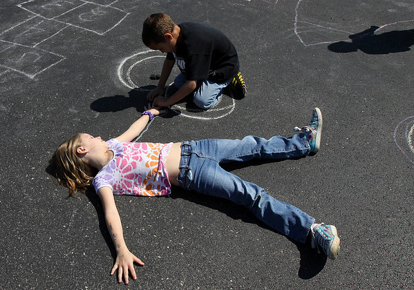 Kayden Caudill traces a chalk outline of Kaydence Heineman while attending the YMCA of Southern Indiana spring break camp in Jeffersonville. Staff photo by C.E. Branham