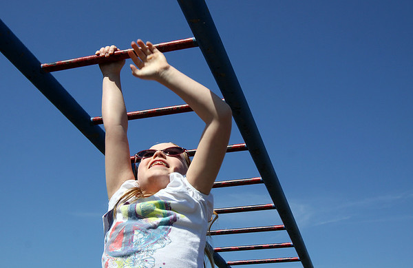 Alise Schaaf makes her way across the monkey bars while attending the YMCA of Southern Indiana spring break camp. Staff photo by C.E. Branham