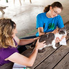 Christina Branstetter, 18, of New Washington, right, comforts Dolly, her domestic American short hair cat, while Denise Allgeier, of Charlestown, judges her during the cat show at the Clark County 4-H Fair on Saturday afternoon. Staff photo by Christopher Fryer
